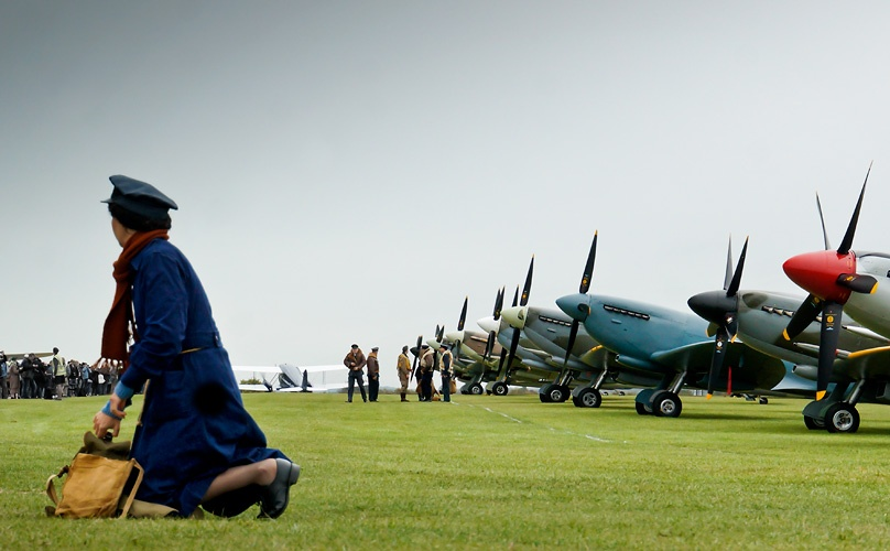 Blog, Battle of Britain airshow. Spitfires on grass, pilots in period uniform. WRAF officer in foreground.