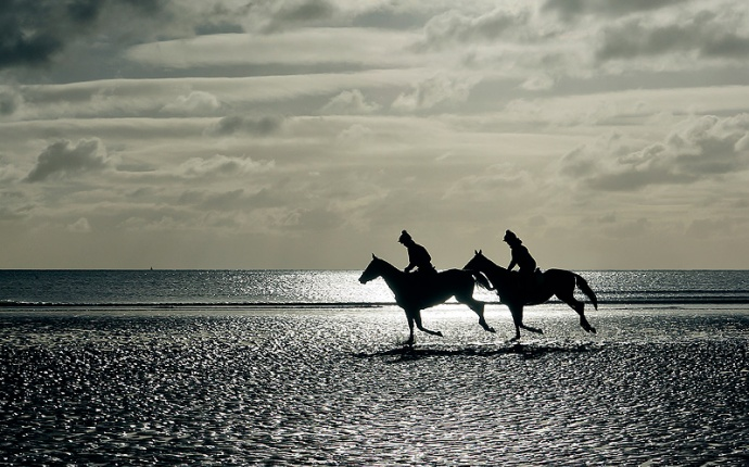 Seascape. two horses and riders galloping on sunlit beach in winter.