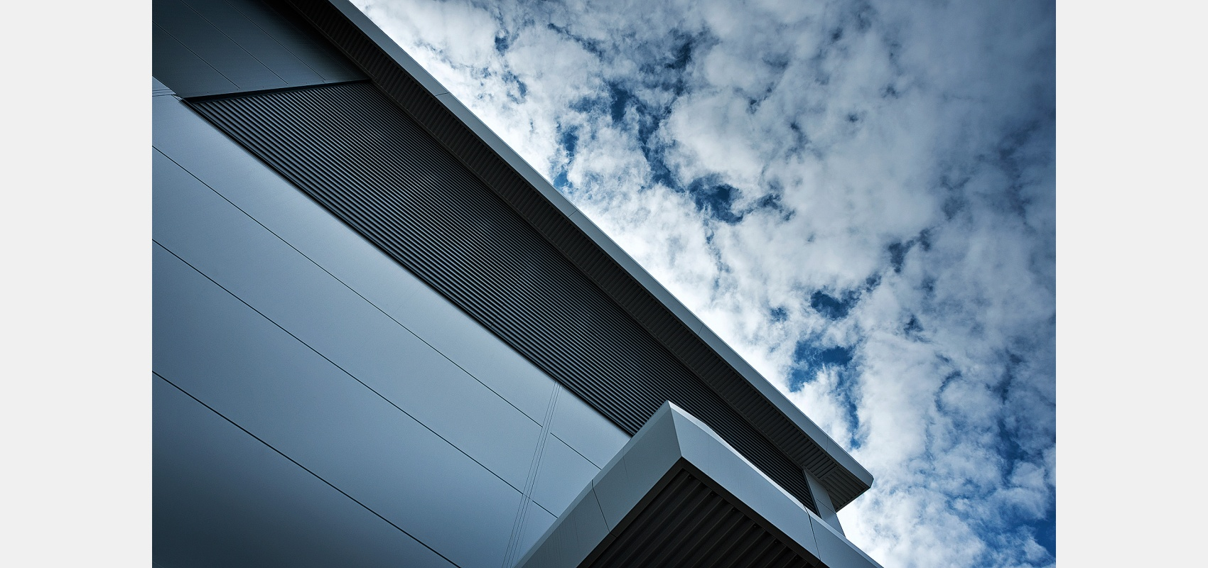 Construction Photography/ Exterior finish/ new lab against mottled sky.