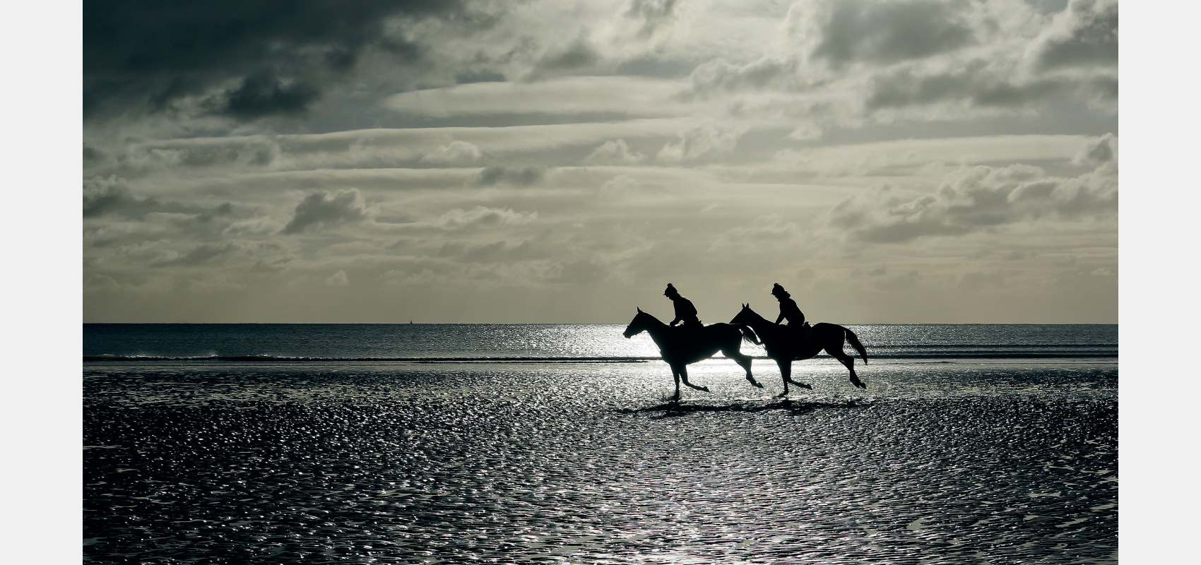 Location - horses and riders exercising on winter beach.