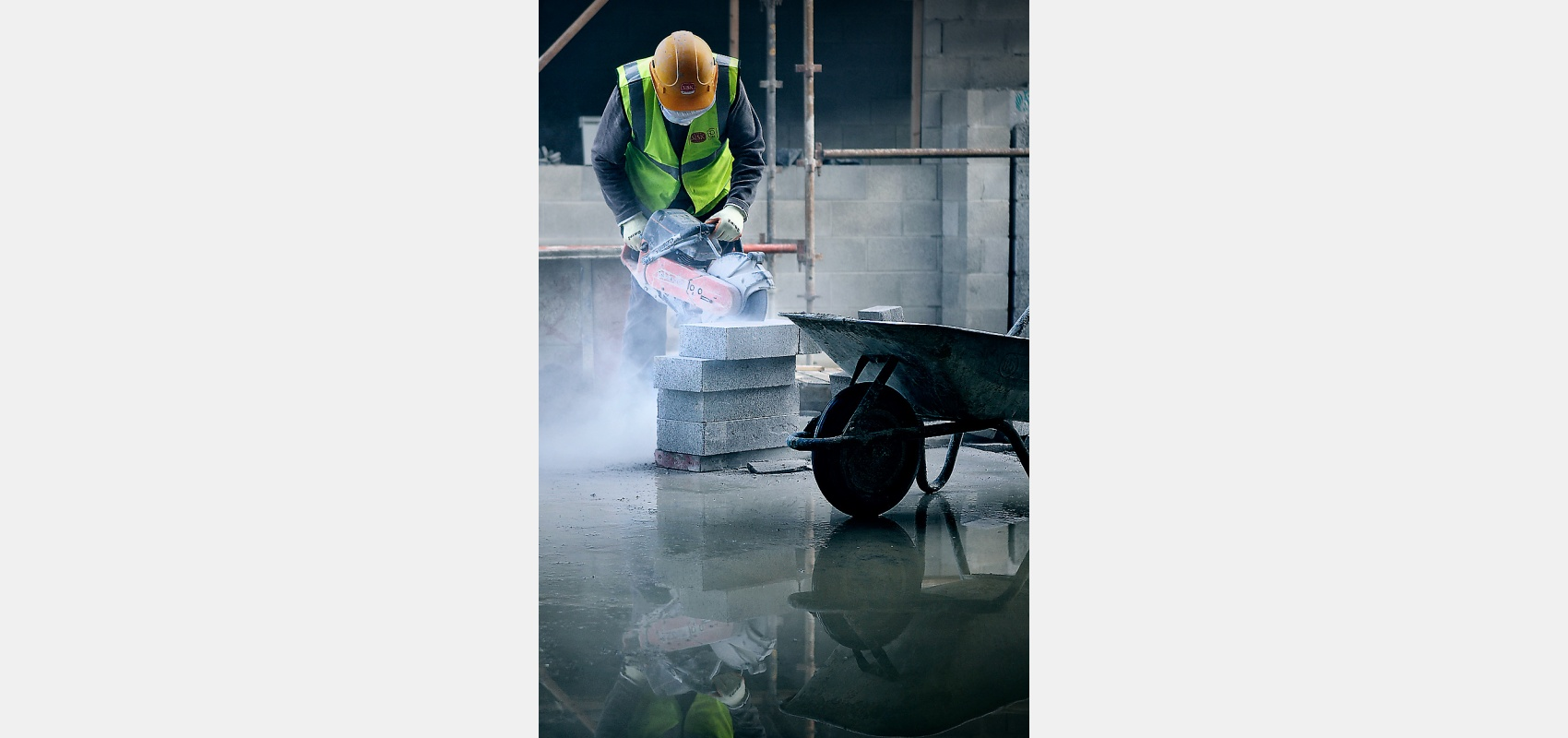 Construction worker,cutting,breeze blocks,water,reflection,foreground.